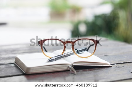 Relax time concept to show by pen and glasses that place on the open notebook