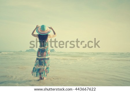 Relax woman standing and looking  on the beach,Summer vacation concept.Vintage tone. - stock photo