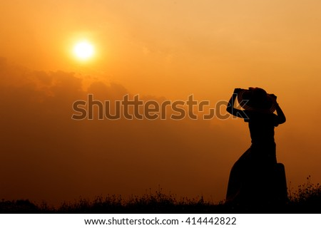 Relax woman with a suitcase on a meadow  at sunset silhouette.Holiday summer travel concept
