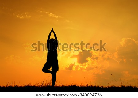 Relax yoga woman and sunset silhouette with copy space. - stock photo