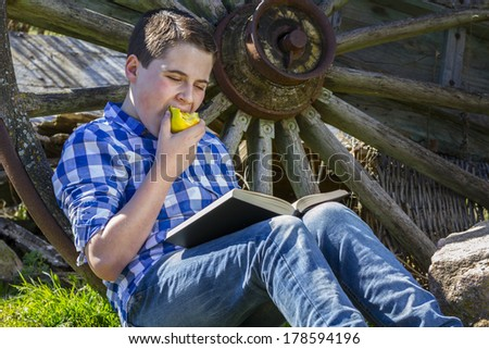 Relax.Young boy reading a book in the woods eating an apple - stock photo
