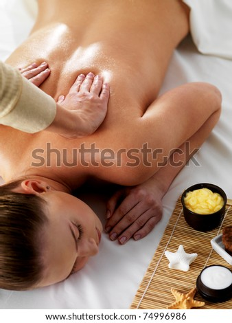 Relaxation and joy in massage for young beautiful woman in spa beauty salon - vertical - stock photo