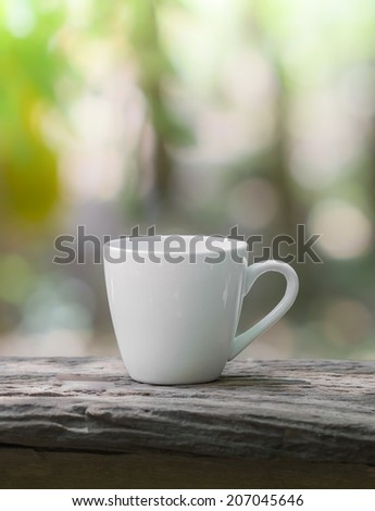 relaxation corner with coffee cup on plank, green forest background