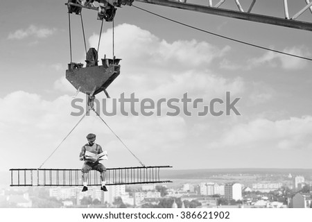 Relaxation needed. Black and white shot of a retro builder reading a newspaper sitting on a crossbar above the city - stock photo