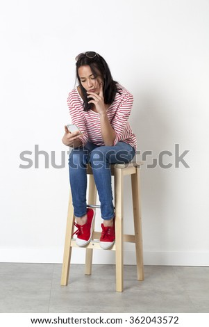 relaxation on the phone - unhappy young multi-ethnic female student thinking in reading her messages on her mobile phone, sitting on a stool, white background - stock photo