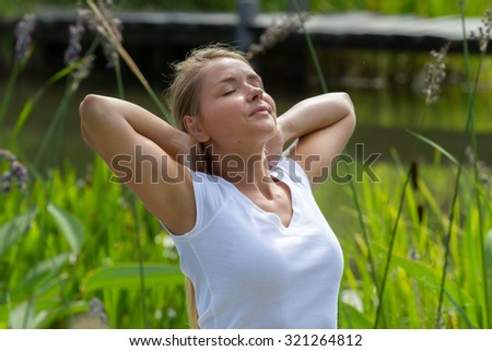 relaxation outdoors - happy young woman breathing,enjoying sun and vacation with green surrounding, summer daylight - stock photo