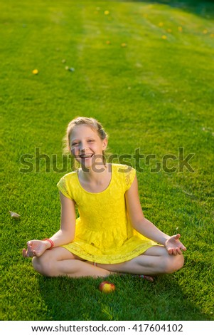 Relaxation with yoga in the park. Little girl knows that sport is very useful for her health. Healthy lifestyle for children. Clean air to breathe outdoors. - stock photo
