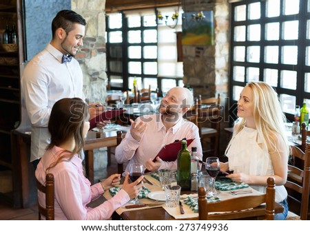 Relaxed adults people having dinner and respectful waiter - stock photo