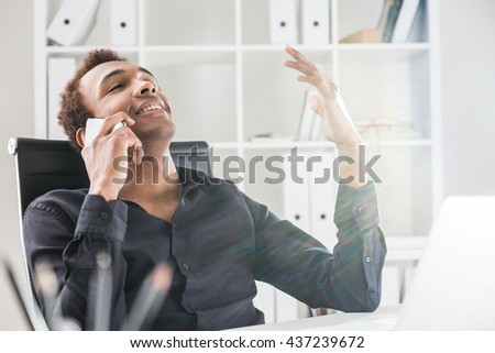 Relaxed african american businessman having phone conversation in office. Bookshelf with documents in the background - stock photo