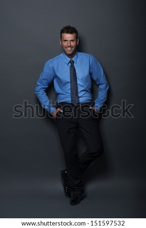 Relaxed and confident businessman looking at camera - stock photo