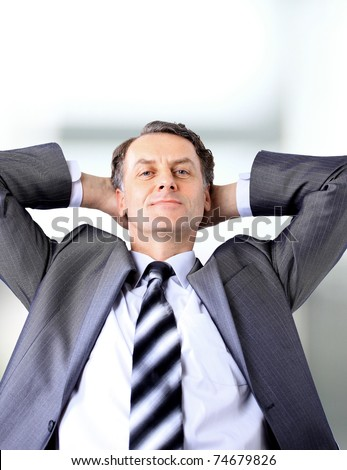relaxed and dreaming business man sits on office chair