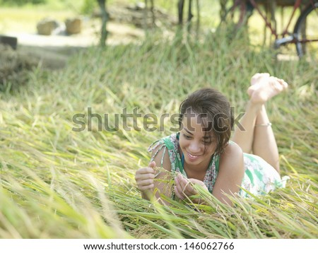 Relaxed and happy young mixed race woman lying in meadow