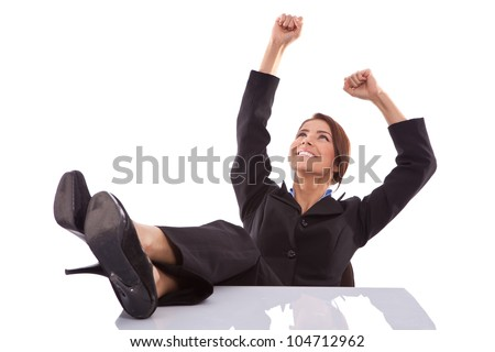 relaxed and winning business woman sitting with her legs on desk and hands in the air - stock photo