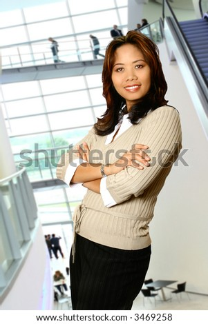 Relaxed asian businesswoman in a modern corporate interior.