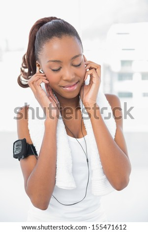 Relaxed athletic woman listening to music in bright fitness studio