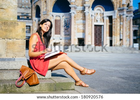 Relaxed beautiful female college student reading outside in european university campus. - stock photo