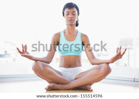 Relaxed black haired woman doing yoga in a living room - stock photo