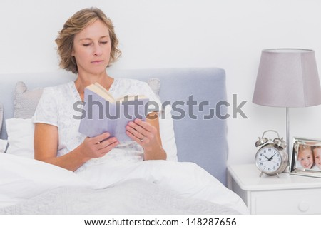 Relaxed blonde woman sitting in bed reading at home in bedroom