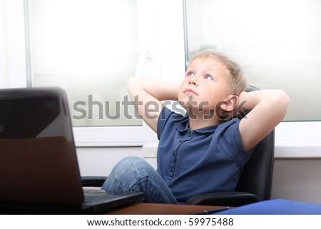 Relaxed boy near laptop. - stock photo