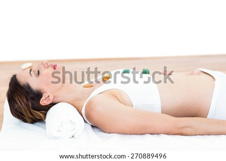 Relaxed brunette lying on mat with stones on white background - stock photo