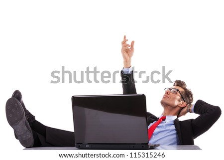 relaxed business man at his desk with laptop, reaching out for something imaginary above