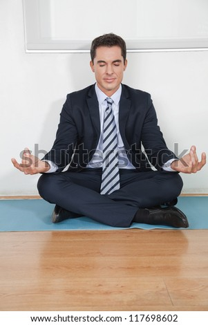 Relaxed business manager doing yoga in his office - stock photo