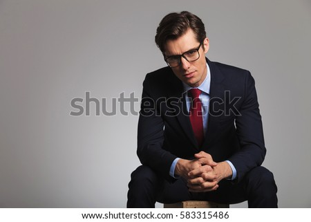 relaxed businessman is sitting and looks at the camera with palms together on grey background