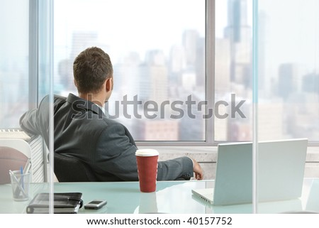 Relaxed businessman sitting at desk in office, looking out the windows to downtown skyscrapers. - stock photo