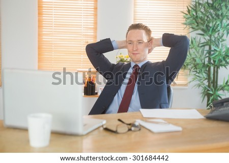 Relaxed businessman sitting back at desk in his office - stock photo