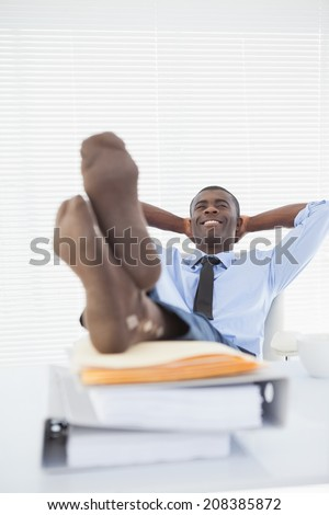 Relaxed businessman sitting in his chair with feet up in his office - stock photo