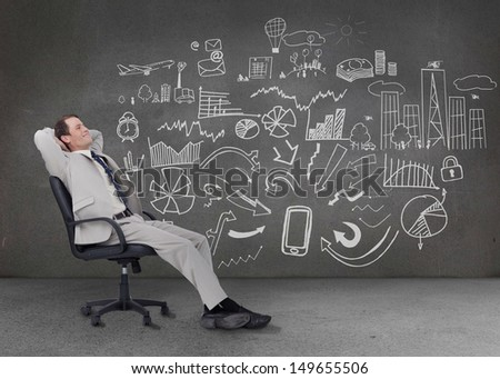 Relaxed businessman sitting on a chair in front of a grey wall with graphs charts and illustrations - stock photo