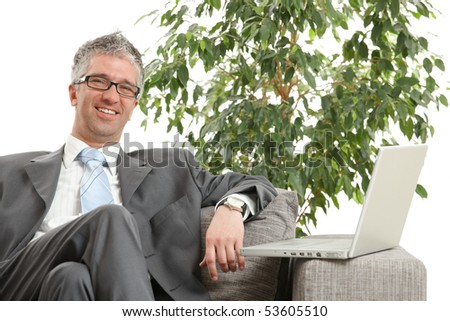 Relaxed businessman sitting on sofa, green office plant in background.