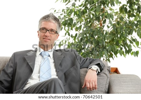 Relaxed businessman sitting on sofa, green office plant in background. ?