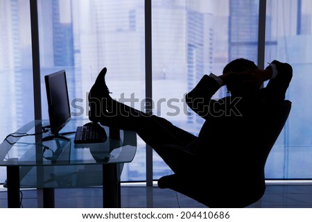 Relaxed businessman sitting with feet up at computer desk in office - stock photo