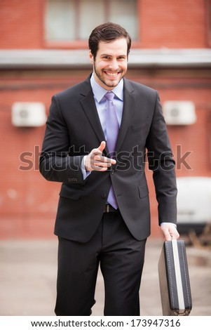 relaxed businessman smiling and walking on the street - stock photo