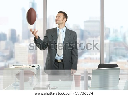 Relaxed businessman standing in front of office windows, playing with football and smiling. - stock photo