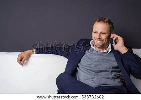 Relaxed businessman taking a call on his mobile phone sitting stretched out on a comfortable sofa smiling with satisfaction