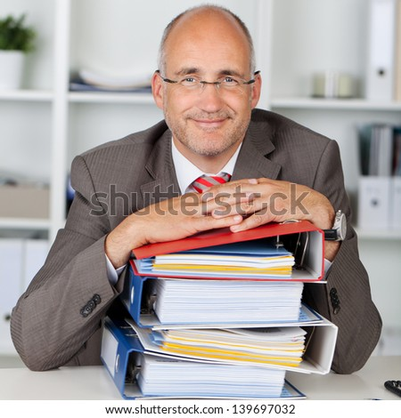 relaxed businessman with a stack of binders on his desk - stock photo
