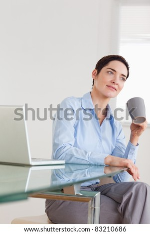 Relaxed businesswoman with a laptop and a cup in an office - stock photo