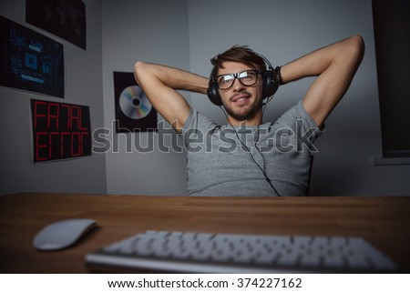 Relaxed carefree young man in glasses sitting with hands behind head and listening to music from computer  - stock photo