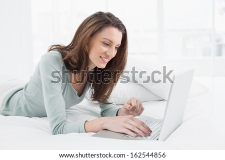 Relaxed casual smiling young woman using laptop in bed at home - stock photo