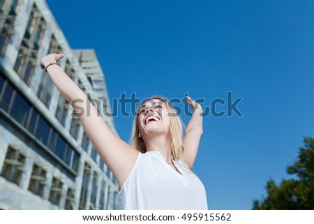 relaxed cheering business woman with copy space in blue sky