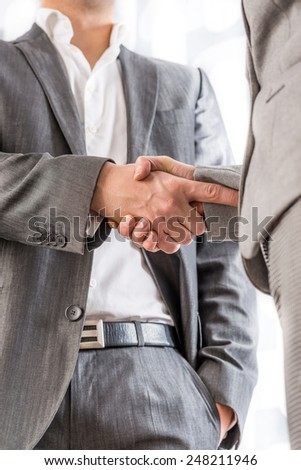 Relaxed confident businessman with his one hand in his pocket standing shaking hands with a client in greeting, congratulations or on the conclusion of a deal between them, low angle view of the hands - stock photo