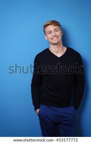 Relaxed confident handsome young blond man with a lovely friendly smile standing with his hands in his pocket against a blue background - stock photo