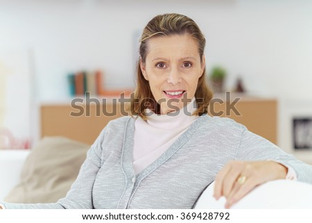 Relaxed confident lady at home in the living room sitting on a sofa looking at the camera with a friendly warm smile, close up view
