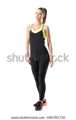 Relaxed content young female athlete in black sports clothing posing at camera. Full body length portrait isolated on white background.