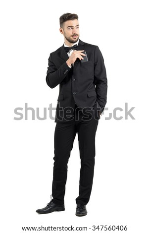 Relaxed cool handsome man in tuxedo with bow tie putting mobile phone in pocket looking away.  Full body length portrait isolated over white studio background.
