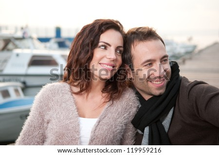 Relaxed couple on wooden pier - stock photo