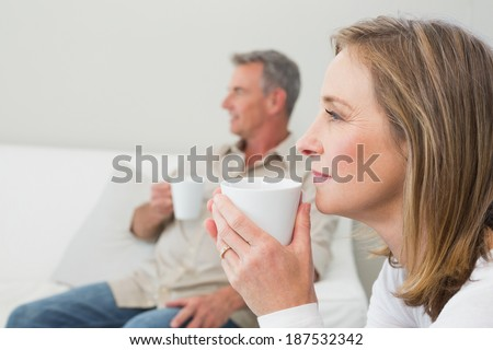 Relaxed couple with coffee cups in living room at home - stock photo