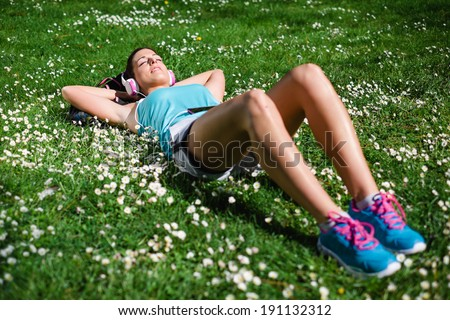 Relaxed female runner resting and relaxing after running training. Woman lying down and day dreaming on grass and spring flowers. Healthy lifestyle and happiness concept.